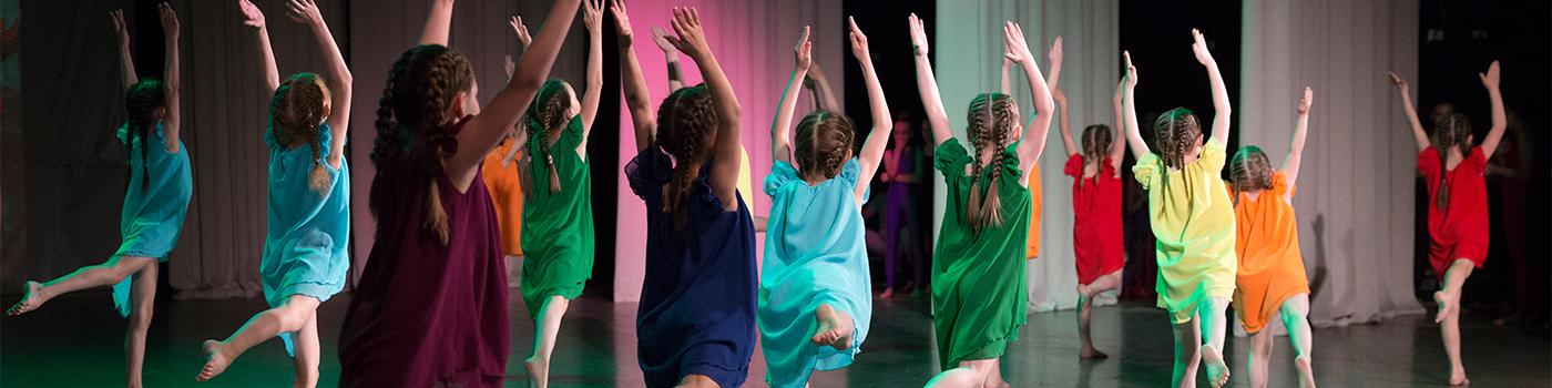 Eine Gruppe von Mädchen in bunten Kleidern tanzt synchron auf einer Bühne