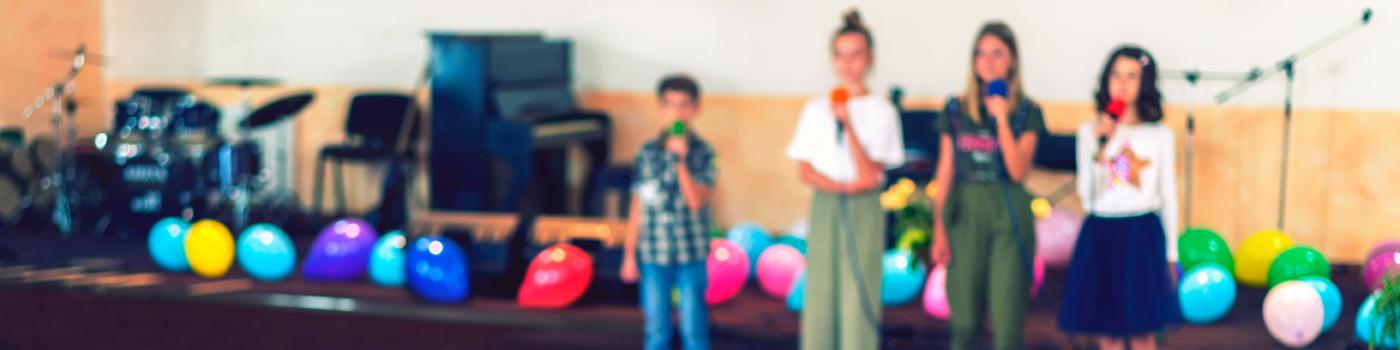 Vier Kinder mit Mikrofonen auf der Bühne