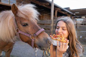 Kind mit Pizza und Pferd